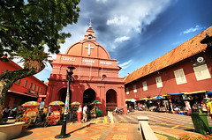 Malacca's Stadthuys Square (` Toshio ') Tags: flowers blue trees red christchurch sky people building church fountain dutch architecture clouds square religious asia religion malaysia malaysian melaka malay malacca redbuilding stadthuys portugese toshio stadthuyssquare