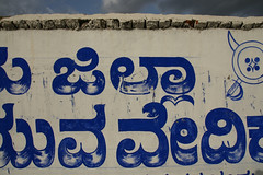 crossed swords, with button (romana klee) Tags: blue white painterly wall writing logo intense paint letters vivid line button shield form script outline swords mysore organization association brushstrokes alignment kannada