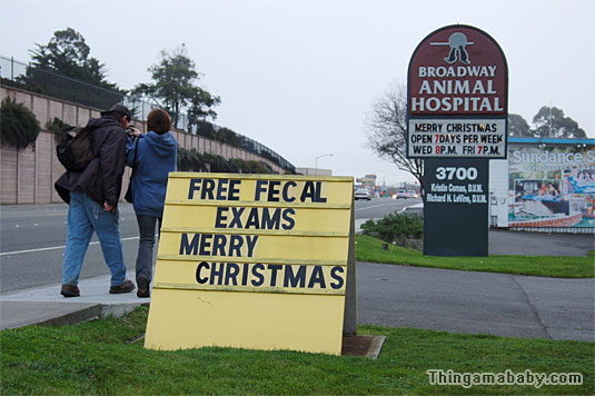 Photo of a yellow sandwich board near a sidewalk which reads: Free fecal exams, Merry Christmas. In the background is a permanent sign for Broadway Animal Hospital.