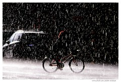 Biking in the Rain (Araleya) Tags: araleya stockholm sweden rainfall downpour bicycle rainstream summer scandinevian weather season climate rain raining afternoon lighting exposure scandinevia streetshot life lifestyle citylife street urban moment road people fz50 panasonic lumix leica i500 interestingness explore zen frozenmoment