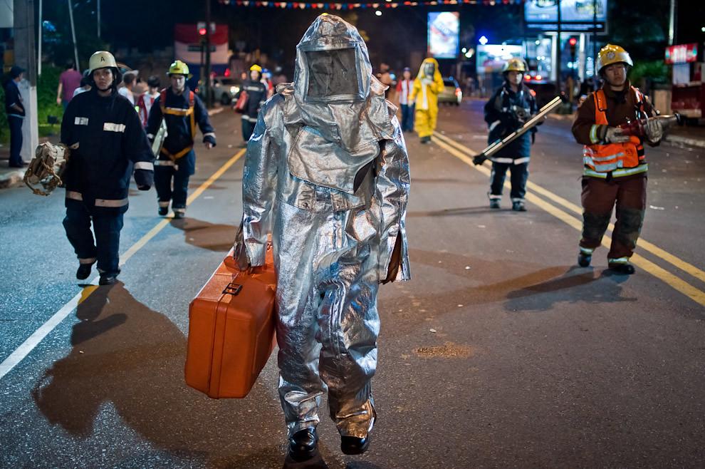 Un efectivo del Cuerpo de Bomberos (los azules) camina con su traje de protección al final del Desfile de representaciones de los pueblos originarios, inmigrantes, de carnavales de Paraguay y de naciones invitadas el sábado 14 de Mayo. (Elton Núñez - Asunción, Paraguay)
