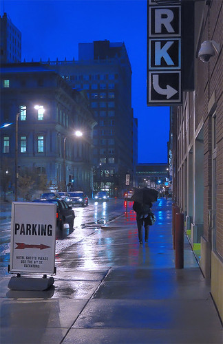 Parking sign, pedestrian with umbrella, in downtown Saint Louis, Missouri, USA - at dusk in the rain