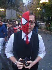 Man wearing half a Spiderman mask and a black vest over a tie.