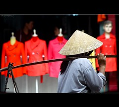 Vietnam | Hue city: Conical hat and winter fashion~ (Vu Pham in Vietnam) Tags: street city red fashion photography asia southeastasia vietnamese vietnam explore vendor non hue vu 2009 tailor indochina hué việtnam conicalhat huế việt nónlá thờitrang raininvietnam commentwithimageswillbedeletedsosorryforthis thợmay