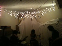 A blurry picture of a 3 piece band. They play beneath christmas lights and a banner reading FOC FEST