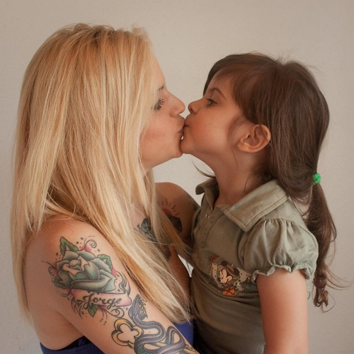 Kissing girl with tattoo arm