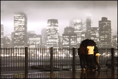 Seems Like Old Times (9/11) (Linus Gelber) Tags: nyc friends newyork rain skyline umbrella lights memorial view manhattan worldtradecenter towers 911 brooklynheights memory promenade eastriver twintowers cinematic beams huddle tributeinlight 911memorial rainynight canon28135mmisusm huddledtogether tributeinlight2009