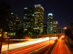 life in the fast lane (Andy Kennelly) Tags: california road city bridge red signs cars skyline architecture speed buildings lights losangeles glow nightshot traffic under palmtree rush freeway getty lightstreams fastlane offramp merging kennelly ajax8055