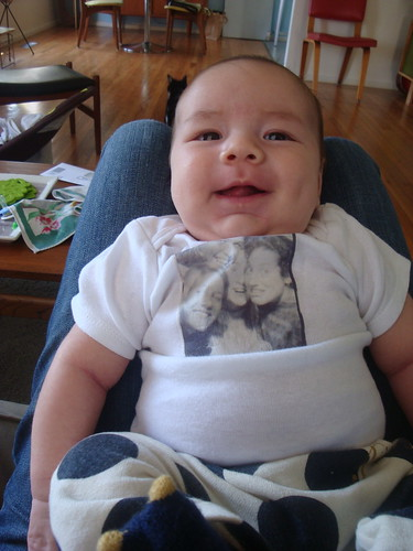 desi wearing his onsie from auntie erin, featuring a screen of one of our famous photobooth sessions from high school