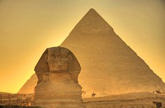 The Giza Sphinx at Sunset (Matt Champlin) Tags: world life old travel sunset horses people orange color history scale sahara sphinx canon landscape ancient glow desert faces pyramid egypt middleeast kingdom size cairo egyptian huge glowing pyramids camels giza dynasty towering gizapyramids khafra mywinners abigfave eos40d thegreatsphinxofegypt