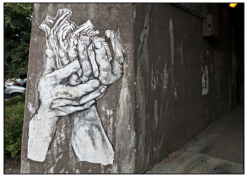 sticker graffiti of two hands gently cupping a heart