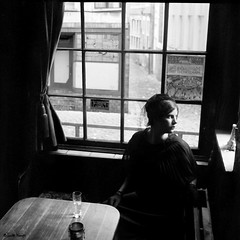 la reverie (moggierocket) Tags: old woman black 6x6 window hat mediumformat table daylight pub shadows view interior drinking oldfashioned rolleicord backintime 500x500 convertedtobw winner500 twinreflexcamera