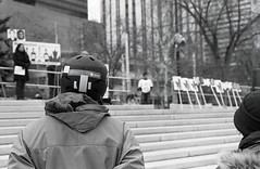 (teh hack) Tags: street camera party people bw canada green film bicycle analog square person photography 50mm bay photo edmonton batch candid rally helmet protest first nb alberta churchill hp5 f2 analogue omar flickrmeet guantanamo gitmo rokkor chrisps khadr