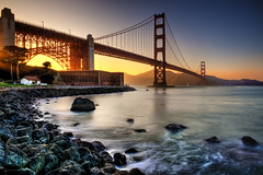 Golden Gate - Golden Light (Surrealize) Tags: ocean sanfrancisco california bridge blue light sunset sea orange house seascape motion reflection tree brick water sailboat landscape golden bay harbor nikon rocks waves ray glow arch purple wideangle landmark structure goldengatebridge gradient fortpoint hdr d700 surrealize