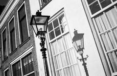 Lantern shadows @ Zwolle (PaulHoo) Tags: contax t2 film analog 35mm neopan zwolle holland netherlands lantern shadow contrast window architecture building light city urban lines diagonal