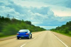 Cruising on the Highway (ashour rehana) Tags: blue trees canada car sedan photoshop one moving highway driving open fast cruising manitoba transcanadahighway speeding subaruimpreza radialblur zoomblur cokin impressedbeauty
