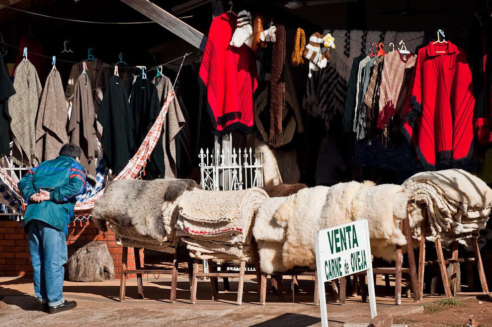 Un visitante se aproxima a una de las tiendas de artesanías y confecciones de lana para realizar una compra en la mañana del sábado 11 de junio, pocas horas antes que comience el festival. Una característica particular de la Ciudad de San Miguel son estas tiendas colocadas a lo largo de toda la zona urbana sobre la Ruta 1. Distribuidas de izquierda a derecha, estas tiendas adornan la ciudad tentando a cualquier persona a hacer una parada para comprarse algo. (Elton Núñez, San Miguel - Paraguay)