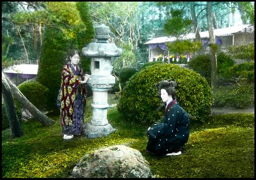 A SQUATTING GEISHA and her ATTENDANT at a PRIVATE GARDEN in OLD YOKOHAMA, JAPAN