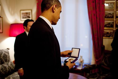 President Barack Obama looks at his Nobel Prize for Peace medal