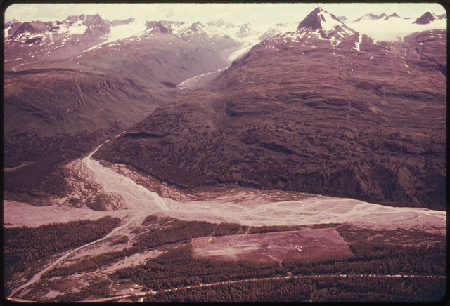 View South Across the Richardson Highway Lower Foreground to the Site of the Sheep Creek Construction Camp (Shown in Preliminary Land Clearing Phase) the Lowe River Wortmanns Creek and Wortmanns Glacier (Center Distance)081974 by The US National Archives