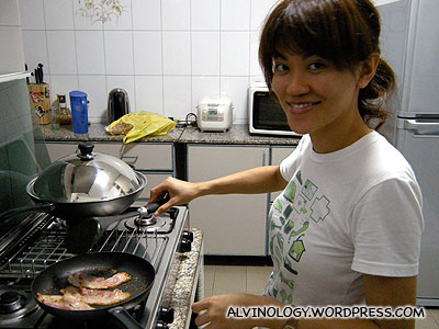 Rachel cooking some bacons and eggs to go with the bread