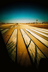 Runway at Sky Harbor Airport (kevin dooley) Tags: runway skyharbor airport phoenix phx az arizona run way airplane window white stripes whitestripes tire marks horizon vignette pavement plane orange leaving jet fly flying takeoff preparing viv vivalaviv vivitar ultra wide slim vivitarultrawideandslim vivitarultrawideslim lomo lomography film analog kodak elitechrome ebx 100 35mm 22mm extra ang