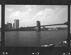 The Brooklyn Bridge viewed from a Circle Line cruise 1985 006 - Version 2 (robertklurfield) Tags: leica nyc cruise bw newyork abandoned water blackwhite manhattan piers brooklynbridge eastriver hudsonriver circleline tourboat