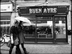Buen Ayre (Che-burashka) Tags: street girls bw london monochrome bike blackwhite couple market streetphotography bn dining hackney broadwaymarket umrella lookingthroughthewindow lx3 locallondon argentiniangrill