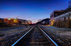 Riding the Rails (KC Mike Day) Tags: rails riding train traintracks parkville missouri town passing by locomotive lights dusk sunset blue yellow buildings horizon rocks gravel wood planks