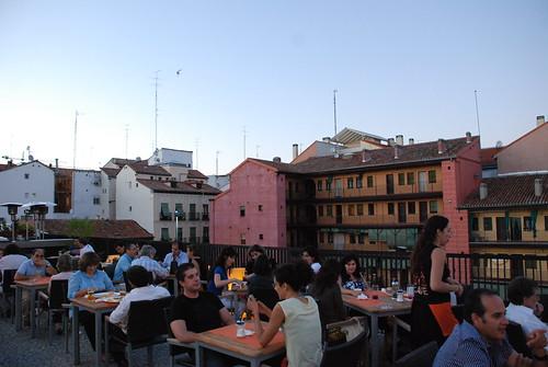 Gente charlando en un restaurante en una terraza con corralas de fondo