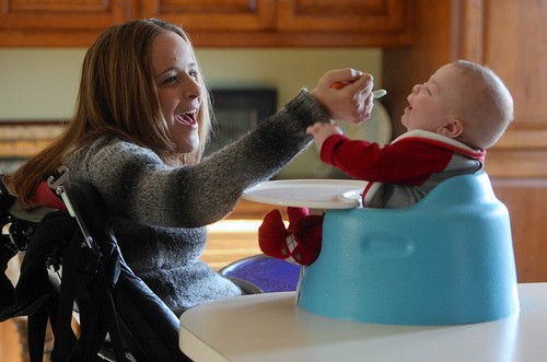 A smiling Kaney O'Neill, sitting in a wheelchair, spoon feeds her baby who is sitting in a Bumbo type seat.