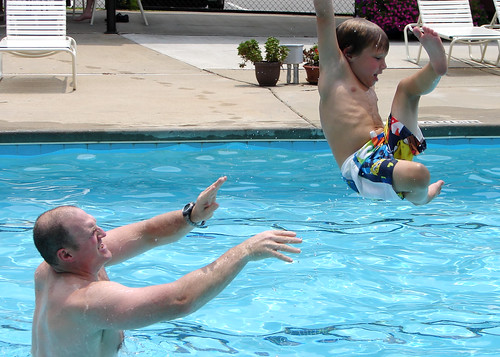 funny photo of kid being thrown into a pool. kid seems to enjoy