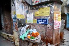 in her crumbling nook (Shreyans Bhansali) Tags: old city woman india flower texture up sign peeling painter varanasi walls seller nook crumbling uttarpradesh