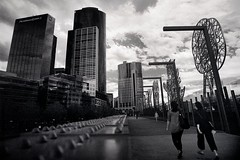 road to mammon (reprise) (mugley) Tags: street city bridge sky people urban blackandwhite bw blur 120 film lines metal skyline architecture modern clouds rollei buildings mediumformat walking prime hotel vanishingpoint 645 rivets dof skyscrapers steel towers australia melbourne wideangle victoria casino scan southbank negative rows pedestrians epson bolts crown polarizer 6x45 r3 sculptures mamiya645 urbanlandscape redfilter wideopen xtol f35 polariser pricewaterhousecoopers aligned freshwaterplace 25a v700 sandridgebridge mamiya645protl m645 rolleir3 thetravellers nadimkaran 35mmf35sekorn 32crop