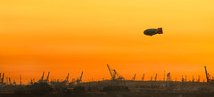 Lead Zeppelin (mbromberger) Tags: sunset sky orange silhouette skyline germany landscape flying dock harbour crane dusk pano aviation air horizon hamburg transport zeppelin pollution airship elbe dirigible printsavailable peute nikond3 nikkor70300mm4556g artflakes