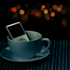 music is like coffee to my senses (alvin lamucho ) Tags: light red music orange green apple cup coffee yellow night dark mac ipod bokeh mp3 player mat placemat kuwait concept conceptual metaphor comparison saucer appleipod mangaf hbw ipodclassic canon450d canonrebelxsi alvinlamucho iphoffee