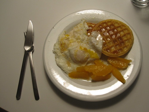 Waffles, orange and eggs with maple syrup