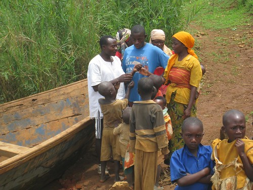 A Rwandan child shows the adults a photo.