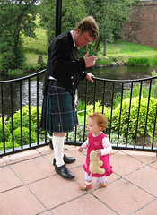 dad_baby_garden = Dad in a kilt watching Speck in the gazebo, with river and greenery in the background