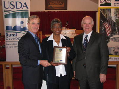 Mable Friend, is presented a plaque in recognition for her dedication and outstanding commitment to the residents of Jonestown by Sen. Ben Cardin and USDA's Jack Tarburton