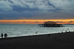 Brighton's West Pier ( Angel of light ) Tags: uk blue sunset people orange beach silhouette walking sussex brighton seagull getty gettyimages licenced coastuk angeloflight2009 licencedbygetty welcomeuk
