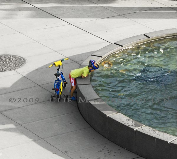 colorful young boy gazing into blue pool of fountain