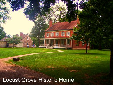 back of locust grove historic home with brick main house with porch grass lawn and stone outbuildings and