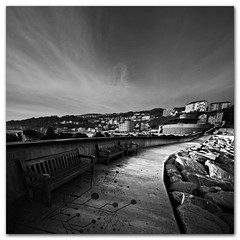 Waiting for the end of the world to come - Ventnor, Isle of Wight. (s0ulsurfing) Tags: uk november winter sea england sky blackandwhite bw white black cold art english water rock composition contrast canon dark bench landscape concrete island vent grey idea mono bay coast town skies britain path empty alien wide perspective wideangle monotone creepy coastal ventnor isleofwight imagination coastline british curve desolate landschaft isle twisted 2009 vector invasion outlet channel creeping englishchannel wight cirrus tendrils discharge expel lamanche 10mm leadinglines sigma1020 s0ulsurfing ventnorbay bratanesque poopalace vertorama chemicalgdnsbenches wastewateroutlet