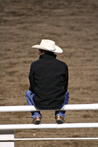 A cowboy watching the proceedings, at the nightly Cody Rodeo in Wyoming.