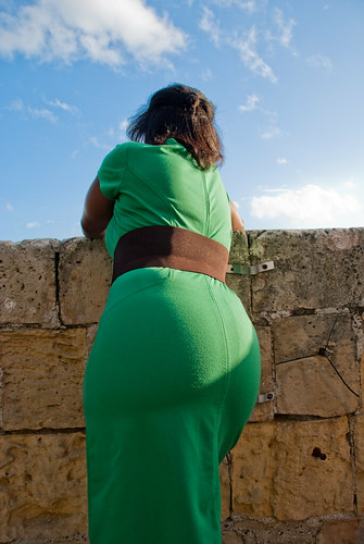 A chubby woman poses her green gown's back