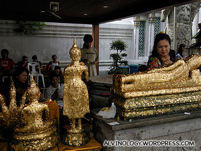 Devotees pasting gold flakes onto various Buddha statues
