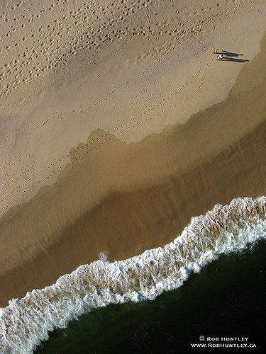 Overhead shot of beach and ocean. Couple walking and their shadows. Playa Arena, Huatulco, Mexico.