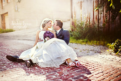 Cobblestone Kiss (dlynnphoto) Tags: wedding love groom bride couple purple bricks plum romance heels aubergine bouquet backlit peoria weddinggown crinoline brickroad greysuit