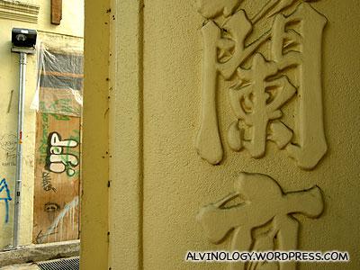 Grafitti art besides old Chinese pillars